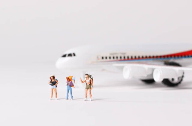 Miniature travelers and toy airplane on white background