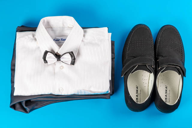 White shirt, trousers and black shoes on a blue background, childrens clothing