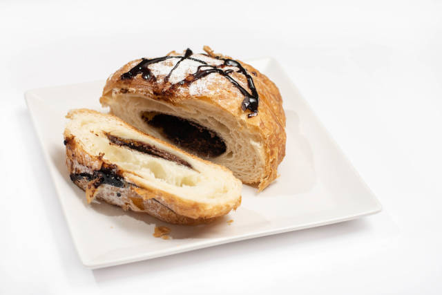 Sliced pastry croisant with chocolate and powdered sugar on the plate