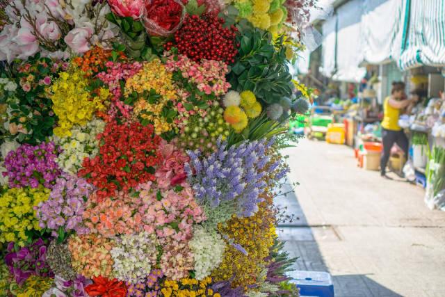 Blumen und der Frischmarkt im Hintergrund. Ho-Chi-Minh-Stadt