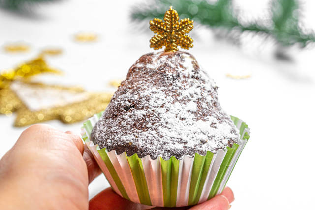 Cupcake in a female hand on a Christmas background
