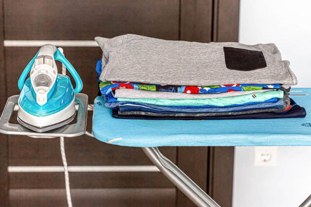 Electric iron with a stack of ironed clothes on blue ironing board