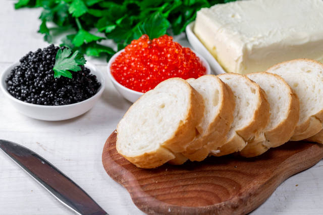 Sliced bread, butter, black and red caviar on the table