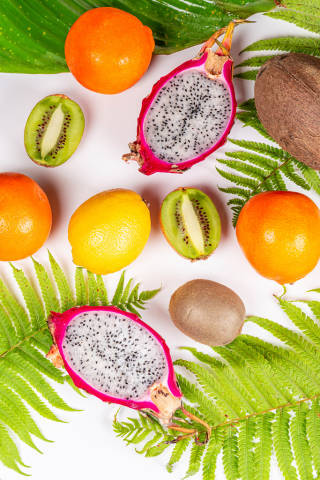 Top view, fresh exotic fruits with green leaves