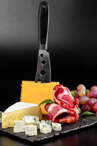 Background of delicious types of cheese and smoked ham with fresh grapes