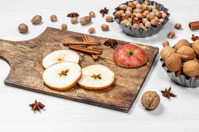 Different nuts, sliced apples and spices on a white background