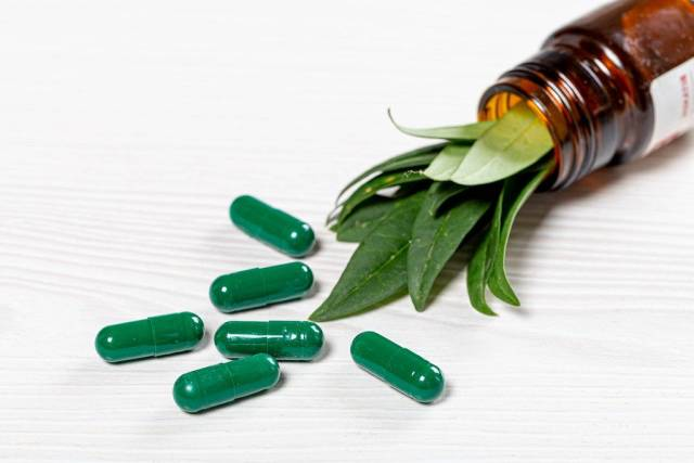 Close-up of green medical capsules with fresh green leaves in a glass bottle (Flip 2019)