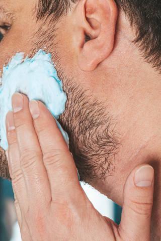 The concept of facial care for men. A man applies shaving gel to his face