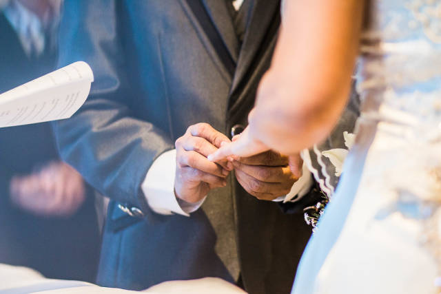 Groom inserting a ring to the Brides finger