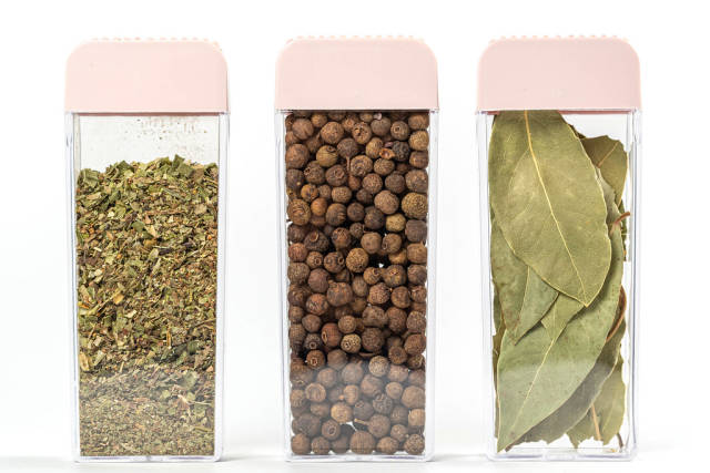 Dried Italian herbs, allspice and bay leaves in containers on white