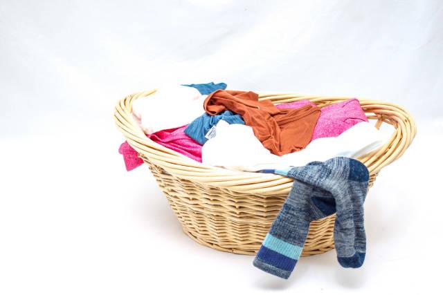 Wäschekorb mit schmutzigen Klamotten vor weißem Hintergrund