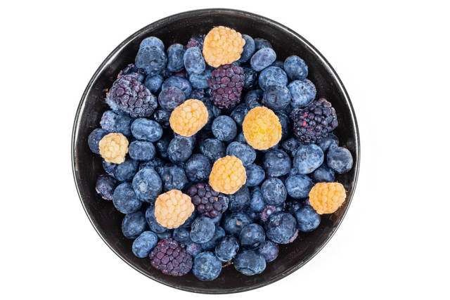 Raspberry, blueberry and mulberry berries in a bowl on a white background, top view