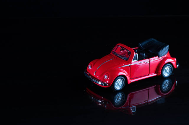Red cabriolet car on black background