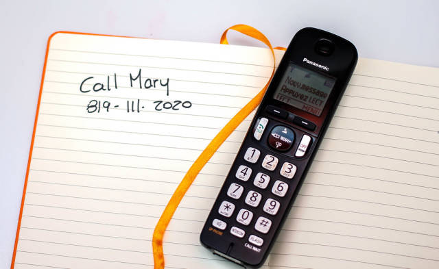 Nahaufnahme von einem Telephone und einem Notizbuch