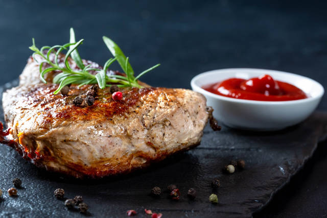 Roast steak with rosemary and spices on black background
