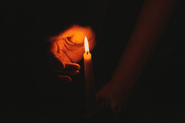 A burning candle at night, protected by the hand of a woman