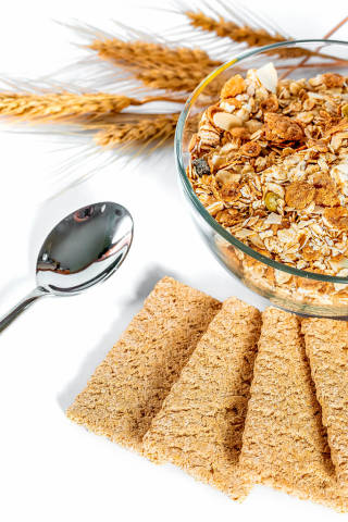 dry briquettes of dietary bread with a bowl of porridge and wheat spikelets on a white table with a spoon