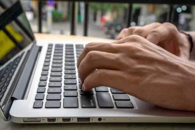Nahaufnahme von  Händen auf Laptop Tastatur- digitaler Nomade arbeitet online