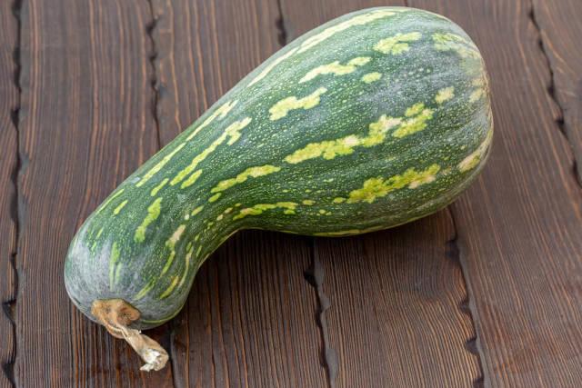 Green edible pumpkin on wooden background