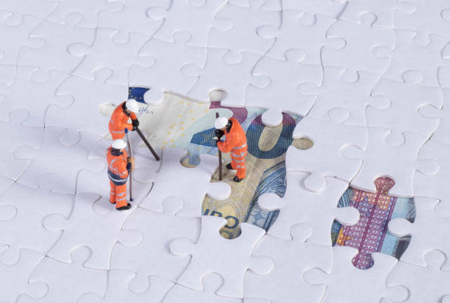 Miniature workers with missing jigsaw puzzle pieces on 20 Euro money banknote