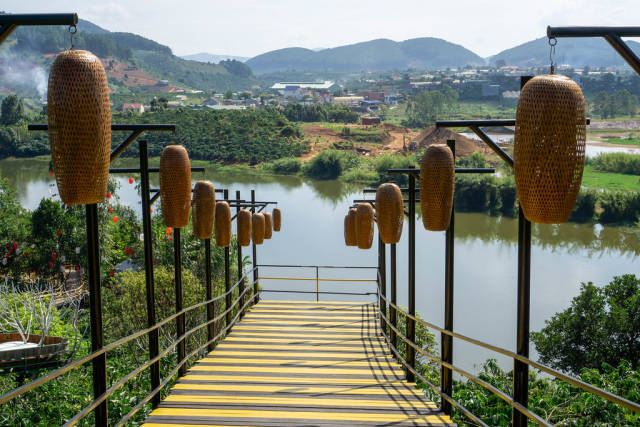 Walkway Bridge with Hanging Lanterns leading to a View of a Lake and Mountains at Me Linh Coffee Garden in Da Lat, Vietnam