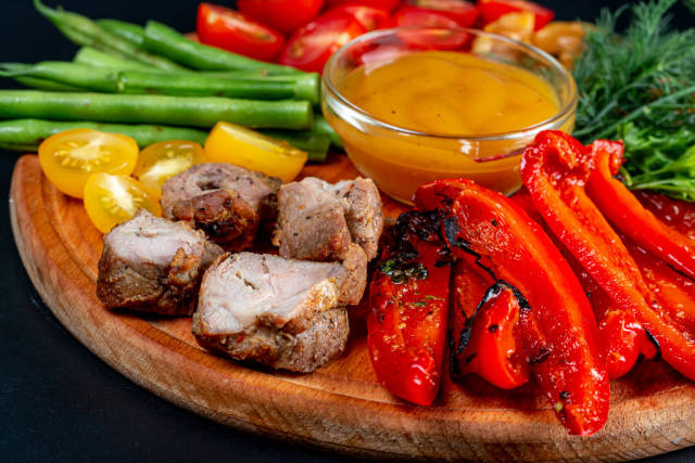 Grilled meat and vegetables on a wooden board with mango sauce