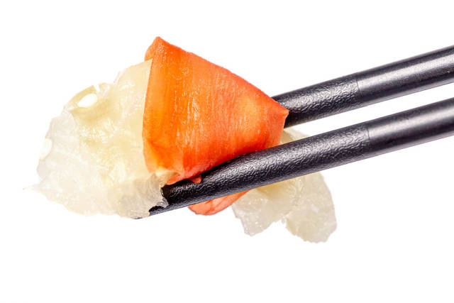 Close-up, a piece of raw fish with pickled ginger in black chopsticks