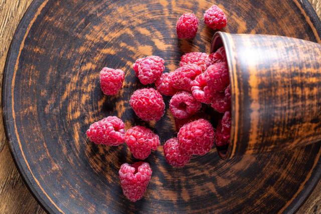 Top view of ripe raspberries on brown plate