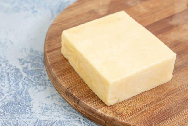 Quadratisches Käsestück auf einem runden Küchenbrettchen aus Holz
