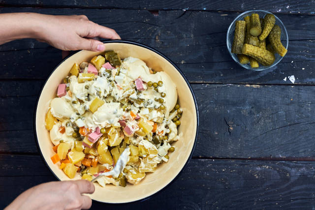 Overhead view of a woman mixing Olivier salad ingredients
