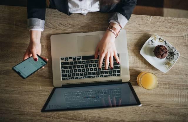 Draufsicht einer Frau, die an ihrem Notizbuch arbeitet