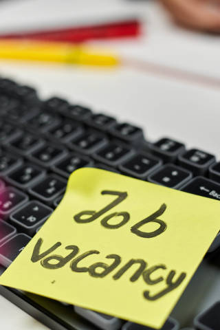 Searching employees. A keyboard and stick note on it with text - Job vacancy