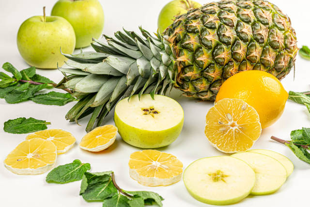 Close-up, pineapple with lemon, apple and mint leaves