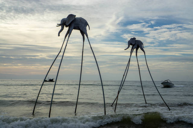 Sunset Photo of Elephant Sculptures on Long Sticks with Fisherboat and Motorboat in the Background at Sunset Sanato Beach Club on Phu Quoc Island in Vietnam