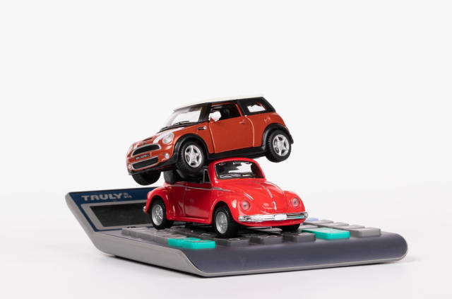 Two toy cars on calculator