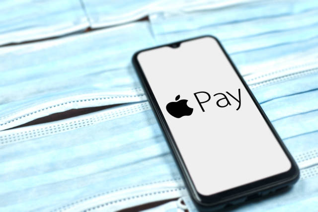 Apple Pay logo on mobile phone over the face masks. Covid-19 effect on company business
