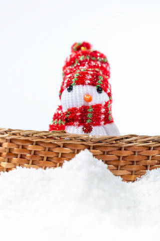Snowman behind the fence with snow