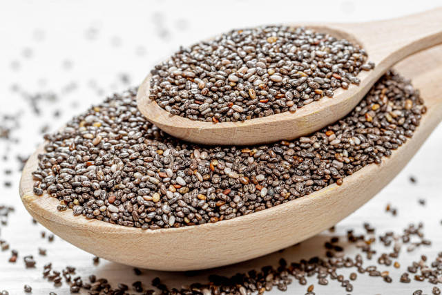 Chia seeds in wooden spoons on wooden table
