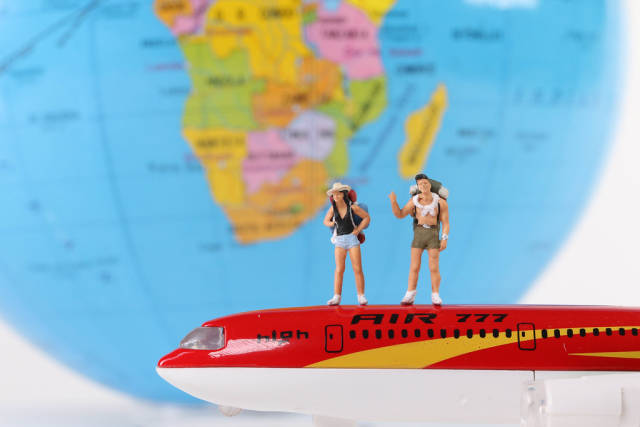 Miniature travelers standing on a red airplane with globe in the background