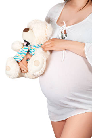 Pregnant girl hugs bear soft toy