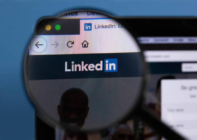 Linkedin-Logo am PC-Monitor, durch eine Lupe fotografiert