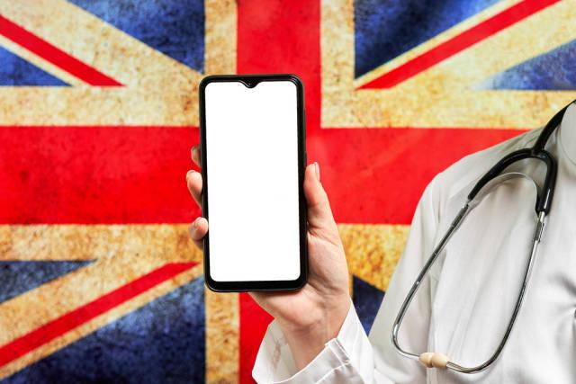 British doctor holds smartphone against flag