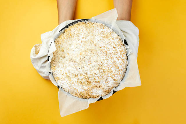 Woman holding freshly baked cottage cheese pie over the yellow background