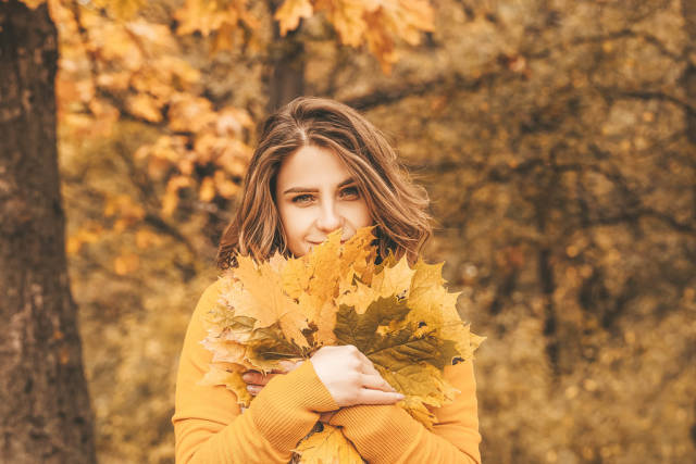 Smiling girl with autumn leaves in the park