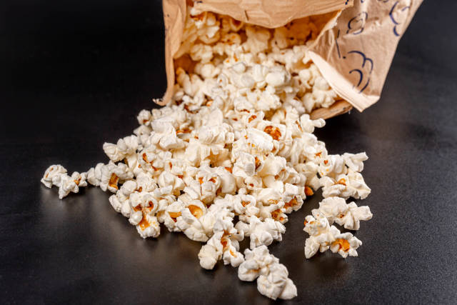 Sweet fresh popcorn poured out on black background