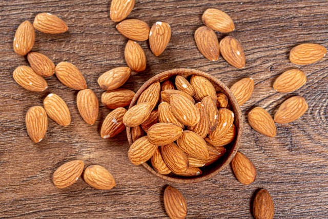 Almond nuts in wooden bowl on brown wooden background. Top view