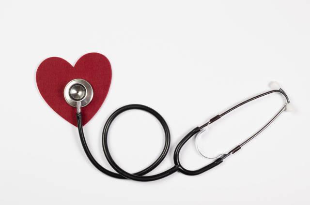 Stethoskop misst Herzschlag eines roten Herzens aus Filz auf weißem Hintergrund