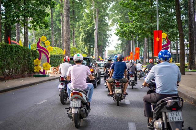 Straße voller Motorroller mit vietnamesischen Flaggen und Dekorationen für das Tet Fest in Saigon