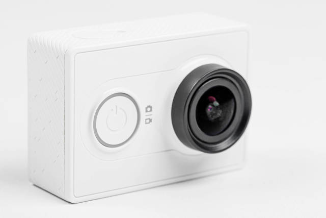 Close up of a white action camera on a white background
