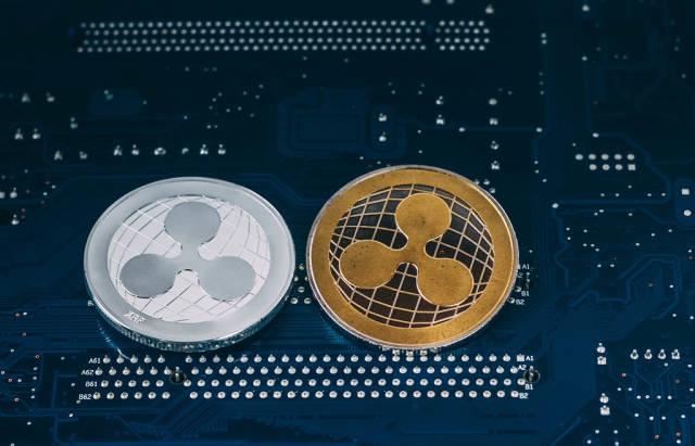 Silberne und goldene Ripple-Münze vor blauem Hintergrund